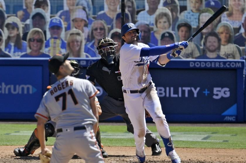 Los Angeles Dodgers' AJ Pollock watches his three-run home run off San Francisco Giants relief pitcher Tyler Rogers.