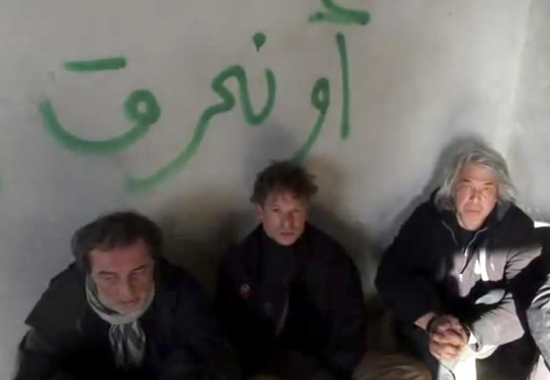 """FILE - In this file image taken from undated amateur video posted on the Internet, NBC chief foreign correspondent Richard Engel, center, with NBC Turkey reporter Aziz Akyavas, left, and NBC photographer John Kooistra are seen after they were taken hostage in Syria. Behind a veil of secrecy, at least 30 journalists have been kidnapped or have disappeared in Syria – held and threatened with death by extremists or taken captive by gangs seeking ransom. The Arabic writing on the wall reads, """"or we will burn."""" (AP Photo/Amateur Video, File)"""