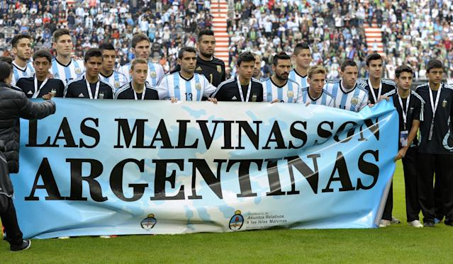 """Argentina's footballers hold a banner reading """"The Malvinas / Falkland Islands are Argentine"""" before a friendly against Slovenia at La Plata stadium in La Plata, Buenos Aires, Argentina on June 7, 2014 (AFP Photo/Alejandro Pagni)"""