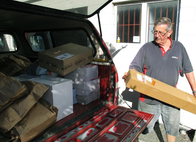 In this photo taken Friday, Feb. 15. 2013, postman John Lahmert loads his truck with mail in Otaki, New Zealand. New Zealand is considering cutting letter deliveries from six days a week to three as global demand for postal services dwindles. (AP Photo/Nick Perry)