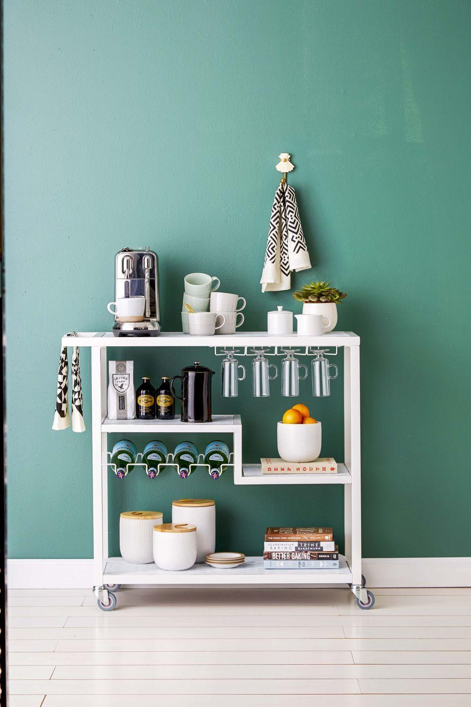 """<p>Turn a bar cart into your local coffeehouse with your <a href=""""https://www.goodhousekeeping.com/appliances/coffee-maker-reviews/g2083/top-rated-coffeemakers/"""" rel=""""nofollow noopener"""" target=""""_blank"""" data-ylk=""""slk:coffee maker"""" class=""""link rapid-noclick-resp"""">coffee maker</a> and mugs within easy reach. Add breakfast bars and dry cereal to the shelves so kids can grab and go. </p>"""