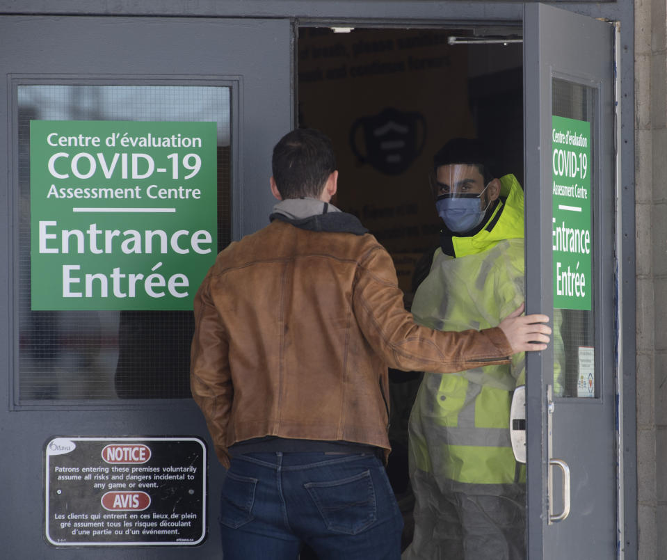 A security guard opens the door for a person entering a COVID-19 assessment facility, Saturday, March 14, 2020 in Ottawa. For most people, the new coronavirus causes only mild or moderate symptoms. For some it can cause more severe illness, especially in older adults and people with existing health problems. (Adrian Wyld/The Canadian Press via AP)