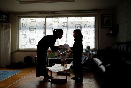 Kim Mi-sung checks her daughter's homework before leaving for school, at their home in Seoul, South Korea, December 19, 2018.  REUTERS/Kim Hong-Ji