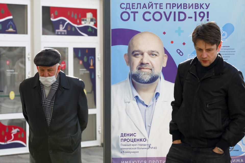 """Two men, one of them wearing a face mask, stand near a vaccination point decorated with the poster showing a portrait of Dr. Denis Protsenko and words reading """"Get vaccinated against covid-19!!"""" at VDNKh, The Exhibition of Achievements of National Economy in Moscow, Russia, Friday, April 2, 2021. Moscow is one of the few places in the world where one can get vaccinated against COVID-19 within hours of deciding to do so. Free doses of the domestically developed Sputnik V shot are readily available for anyone 18 or older at more than 200 vaccination points in state and private clinics, shopping malls, food courts, hospitals and even a theater. (AP Photo/Alexander Zemlianichenko)"""