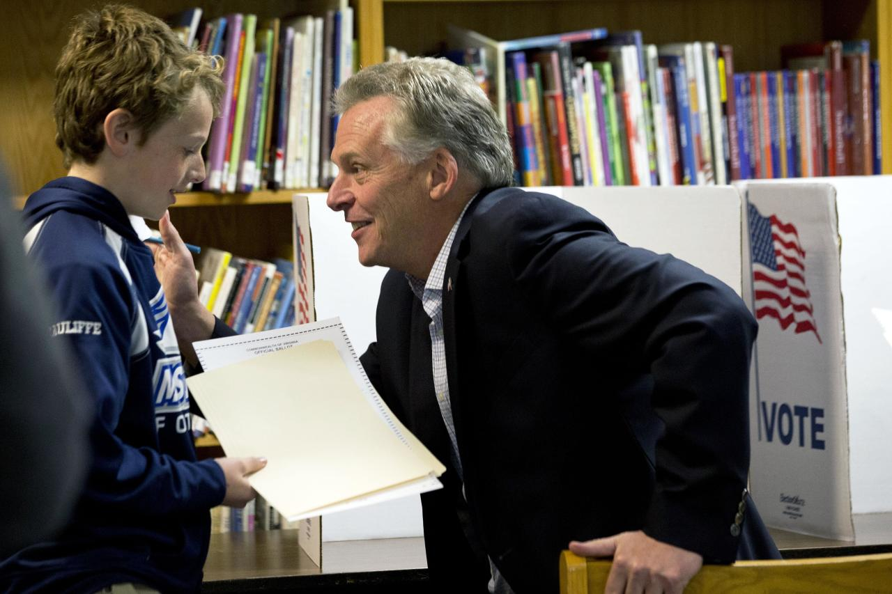 Virginia Democratic gubernatorial candidate Terry McAuliffe, right, turns toward his son Peter after completing his vote on election day in McLean, Va. on Tuesday, Nov. 5, 2013. (AP Photo/Jacquelyn Martin)