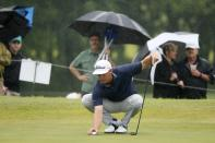 Patton Kizzire works in a pouring rain as he prepares to putt on the 18th green during the final round of the AT&T Byron Nelson golf tournament in McKinney, Texas, Sunday, May 16, 2021. (AP Photo/Ray Carlin)