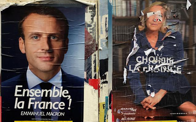 <p>Electoral posters show centrist candidate Emmanuel Macron, left, and a defaced poster of far-right candidate Marine Le Pen, Wednesday May 3, 2017 in Marseille, southern France. Pro-European progressive Emmanuel Macron and far-right Marine Le Pen are facing off today in their only direct debate before Sunday's presidential runoff election. (AP Photo/Claude Paris) </p>
