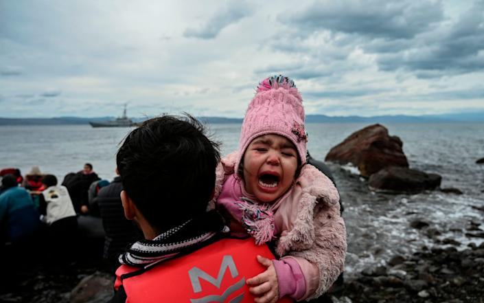 A child cries as a dinghy with 54 Afghan refugees lands ashore the Greek island of Lesbos in February this year - ARIS MESSINIS/AFP