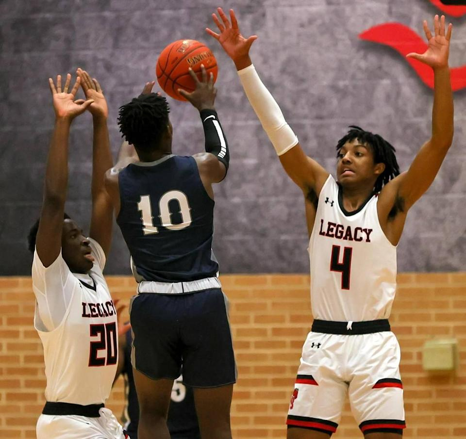 Richland guard Jayden Rhinehart (10) attempts shot against Mansfield Legacy guard John Muhammad (4) and guard Micah Juiye (20) during the first half of a 5A Region 1 Boys Basketball Area-Round 2 playoff game played on February 24, 2021 at Burleson High School. (Steve Nurenberg Special to the Star-Telegram)