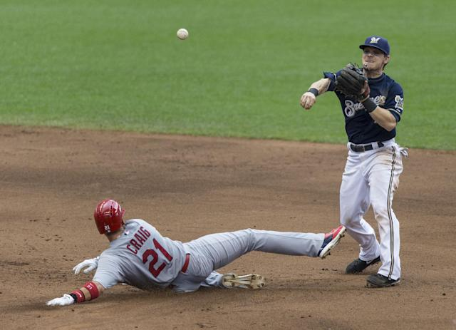 Milwaukee Brewers' Scooter Gennett throws to first after getting the force out at second on St. Louis Cardinals' Allen Craig during the forth inning of a baseball game Sunday, July 13, 2014, in Milwaukee. The throw to first was not in time. (AP Photo/Tom Lynn)