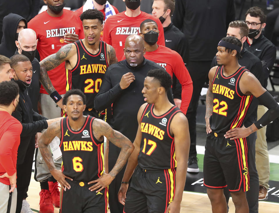 Atlanta Hawks interim head coach Nate McMillan and Lou Williams (from left), John Collins, Onyeka Okongwu, and Cam Reddish look for answers during a time out against the Milwaukee Bucks during the third quarter in game 5 of the NBA Eastern Conference Finals on Thursday, July 1, 2021, in Milwaukee. (Curtis Compton/Atlanta Journal-Constitution via AP)