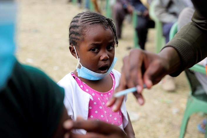 A girl reacts as her father receives an AstraZeneca/Oxford coronavirus disease (COVID-19) vaccine, donated to Kenya by the UK government, in Nairobi, Kenya, August 8, 2021. REUTERS/Baz Ratner     TPX IMAGES OF THE DAY