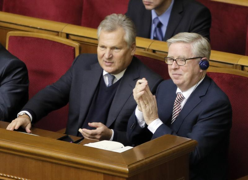 FILE - In this Wednesday, Nov. 13, 2013 file photo, former President of the European Parliament Patrick Cox, right, and former Polish President Aleksander Kwasniewski, watch a parliament session in Kiev, Ukraine. More than 20 years after gaining independence from the Soviet Union and painfully searching for its place on the geopolitical map, Ukraine finally has a real chance to firmly align itself with the EU, with its democratic standards and free-market zone. The alternative is to slide back into Russia's shadow, both politically and economically. (AP Photo/ Efrem Lukatsky, File)