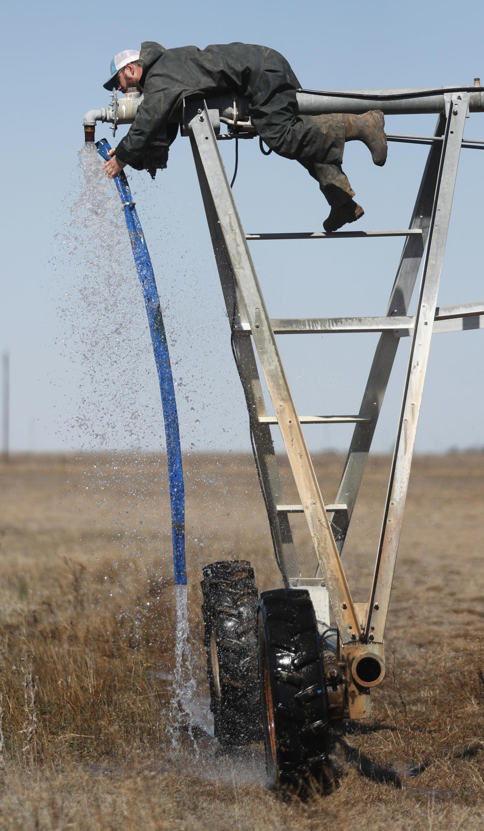 Tyler Black attaches a new sand drain on the end of a pivot on his Muleshoe, Texas, farm on Monday, April 19, 2021, as he prepares to plant grass in a pasture. Black raises cattle and plants pasture in wheat and some native grass – and rations water use -- because the Ogallala Aquifer is being depleted. (AP Photo/Mark Rogers)