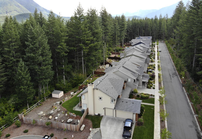 In this photo taken July 24, 2019, a block of houses is surrounded on three sides by a forest in the Cascade foothills of North Bend, Wash. Experts say global warming is changing the region's seasons, bringing higher temperatures, lower humidity and longer stretches of drought. And that means wildfire risks in coming years will extend into areas that haven't experienced major burns in residents' lifetimes. (AP Photo/Elaine Thompson)