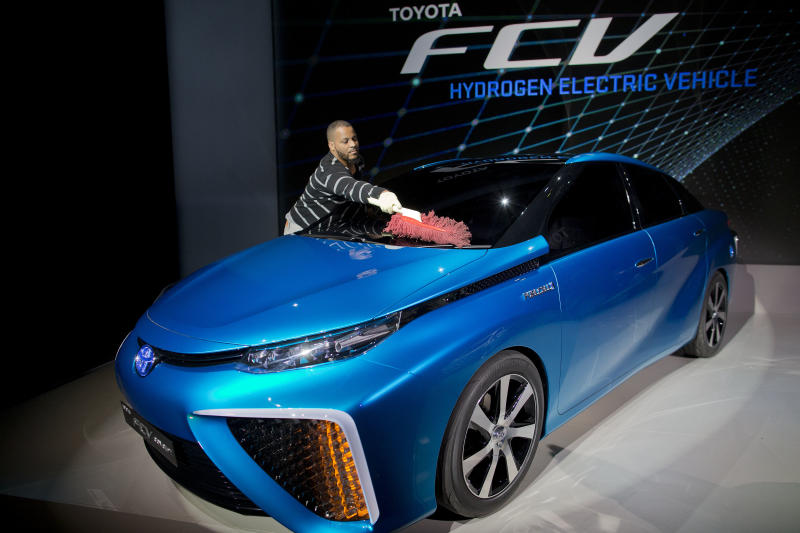 A production crew member dusts off Toyota's FCV hydrogen electric concept car during the International Consumer Electronics Show, Monday, Jan. 6, 2014, in Las Vegas. Toyota announced the car would be available to consumers in 2015. (AP Photo/Julie Jacobson)