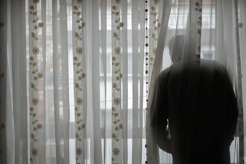 Senior man obeying to curfew looking to empty street from his window (Photo: Canberk Sezer via Getty Images)