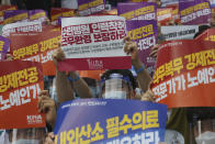 "A doctor holds up a placard during a rally against the government medical policy in Seoul, South Korea, Friday, Aug. 14, 2020. Thousands of doctors in South Korea began a strike Friday in protest of government medical policy, causing concerns about treatment of patients amid the coronavirus pandemic. The signs read: ""Ensure working conditions."" (AP Photo/Ahn Young-joon)"