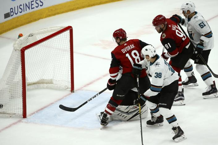 Arizona Coyotes left wing Taylor Hall (91) scores a goal as Coyotes center Christian Dvorak (18), San Jose Sharks defenseman Mario Ferraro (38) and Sharks defenseman Radim Simek (51) look on during the second period of an NHL hockey game Tuesday, Jan. 14, 2020, in Glendale, Ariz. (AP Photo/Ross D. Franklin)