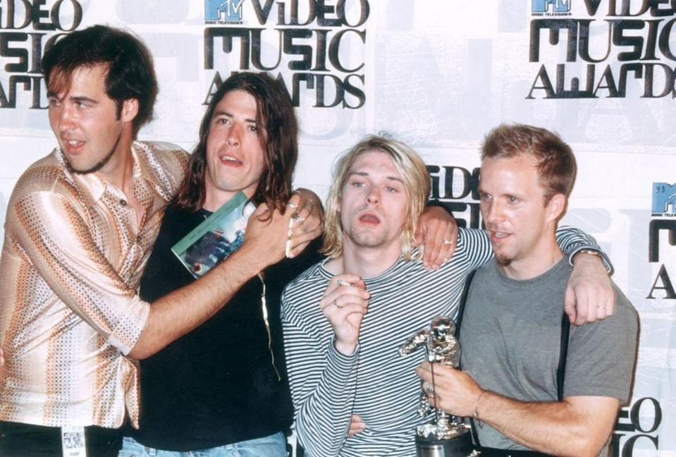 <p>The Seattle-based grunge band, Nirvana, celebrates a win at the MTV Video Music Awards in 1993. Cobain celebrates by lighting up a cigarette on the red carpet.</p>
