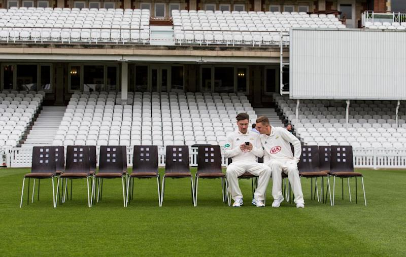 Surrey's Rory Burns (left) and Scott Borthwick grab the best seats before the team group photo at The Oval