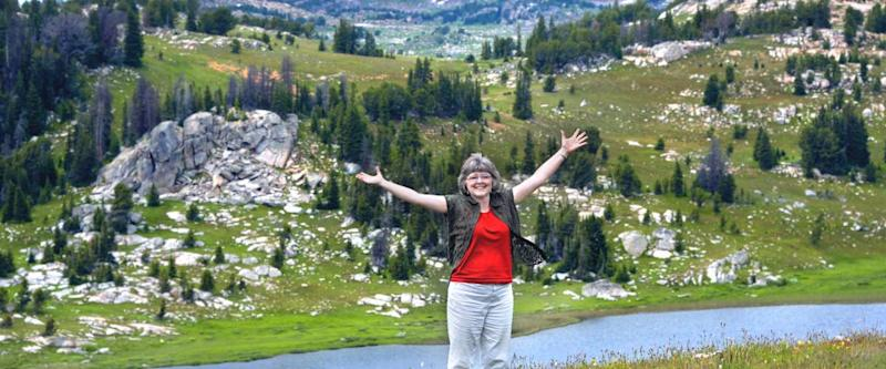 Woman spreads her arms wide to embrace the scenic beauty of Beartooth Pass in Wyoming. She has on a red shirt and khaki pants.