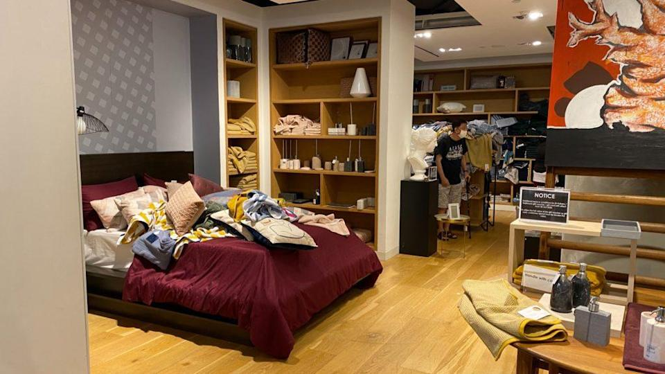 Pillows and bedsheets removed from shelves and left on a bed in the bedding section at The Heeren outlet. Photo: Coconuts