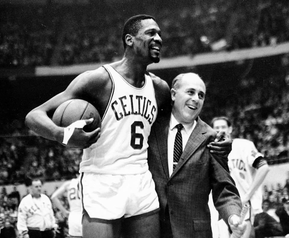 """FILE - In this Dec. 12, 1964 file photo, Boston Celtics' Bill Russell, left,  is congratulated by coach Arnold """"Red"""" Auerbach after scoring his 10,000th career point during a basketball game against the Baltimore Bullets at the Boston Garden in Boston. As a coach, Red Auerbach got the most out of Bill Russell as a player not by yelling at him, or teaching him new techniques. He just talked to him man-to-man. Russell celebrates their relationship in a new book about Auerbach. (AP Photo/Bill Chaplis)"""