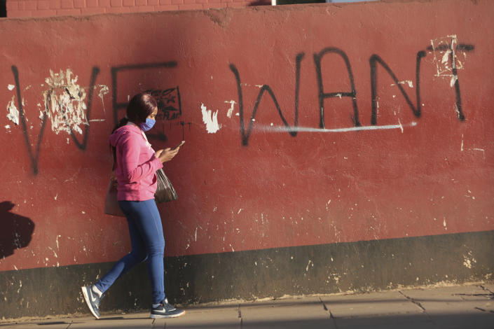 "A woman uses her mobile phone while walking past a wall with graffiti on the streets of Harare, in this Tuesday, July 7, 15, 2020 photo. Unable to protest on the streets, some in Zimbabwe are calling themselves ""keyboard warriors"" as they take to graffiti and social media to pressure a government that promised reform but is now accused of gross human rights abuses.(AP Photo/Tsvangirayi Mukwazhi)"