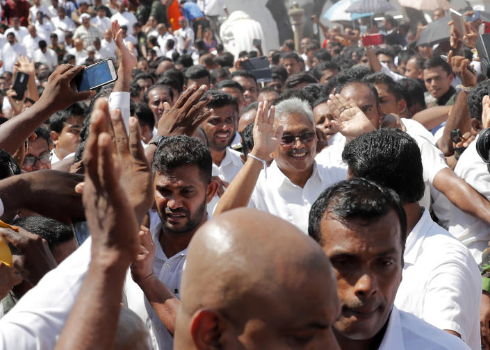 Sri Lanka's newly elected president Gotabaya Rajapaksa, center right, greets people as he leaves after taking the oath of office during the swearing in ceremony held at the 140 B.C Ruwanweli Seya Buddhist temple in ancient kingdom of Anuradhapura in northcentral Sri Lanka Monday, Nov. 18, 2019. The former defense official credited with ending a long civil war was Monday sworn in as Sri Lanka's seventh president after comfortably winning last Saturday's presidential election. (AP Photo/Eranga Jayawardena)