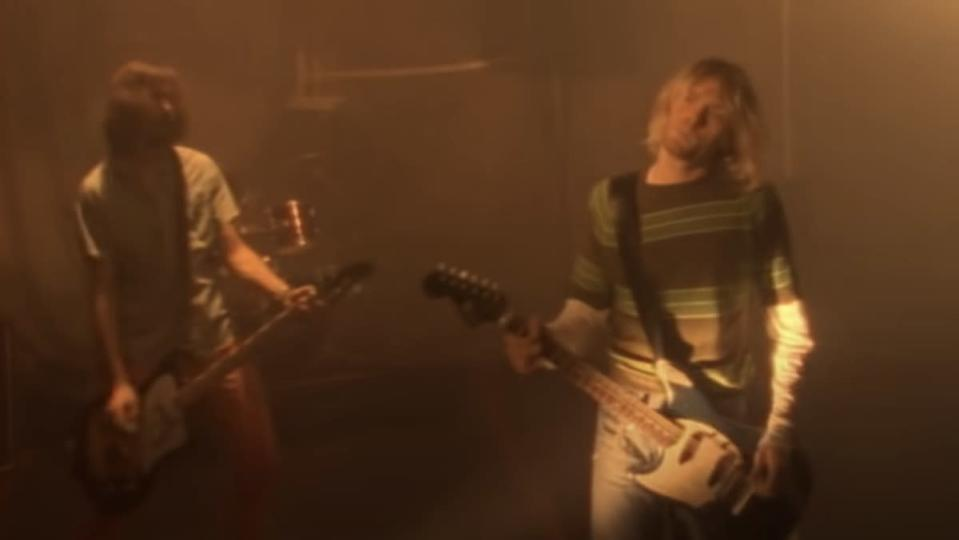 "Kurt Cobain and Krist Novoselic in front of a basketball net Nirvana's ""Smells Like Teen Spirit"" video"
