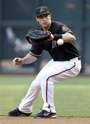 Arizona Diamondbacks second baseman Aaron Hill fields a ground ball hit for an out by Atlanta Braves' Michael Bourn in the second inning of a baseball game on Saturday, April 21, 2012, in Phoenix. (AP Photo/Paul Connors)