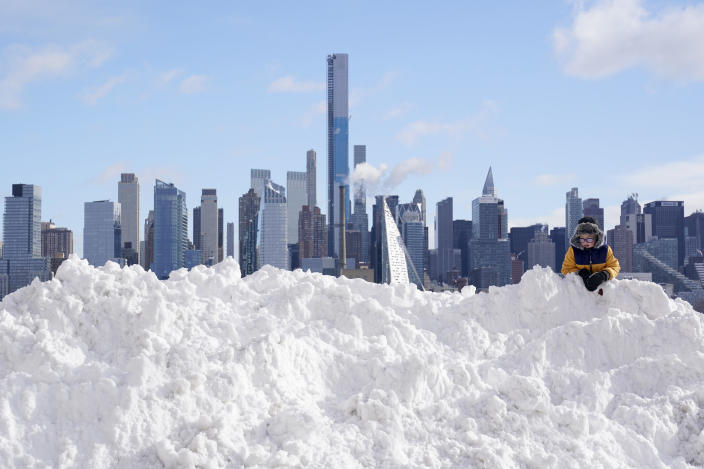 A boy plays on a mound of snow in front of the skyline of New York City in West New York, New Jersey, Thursday, December 17, 2020. / Credit: Seth Wenig / AP