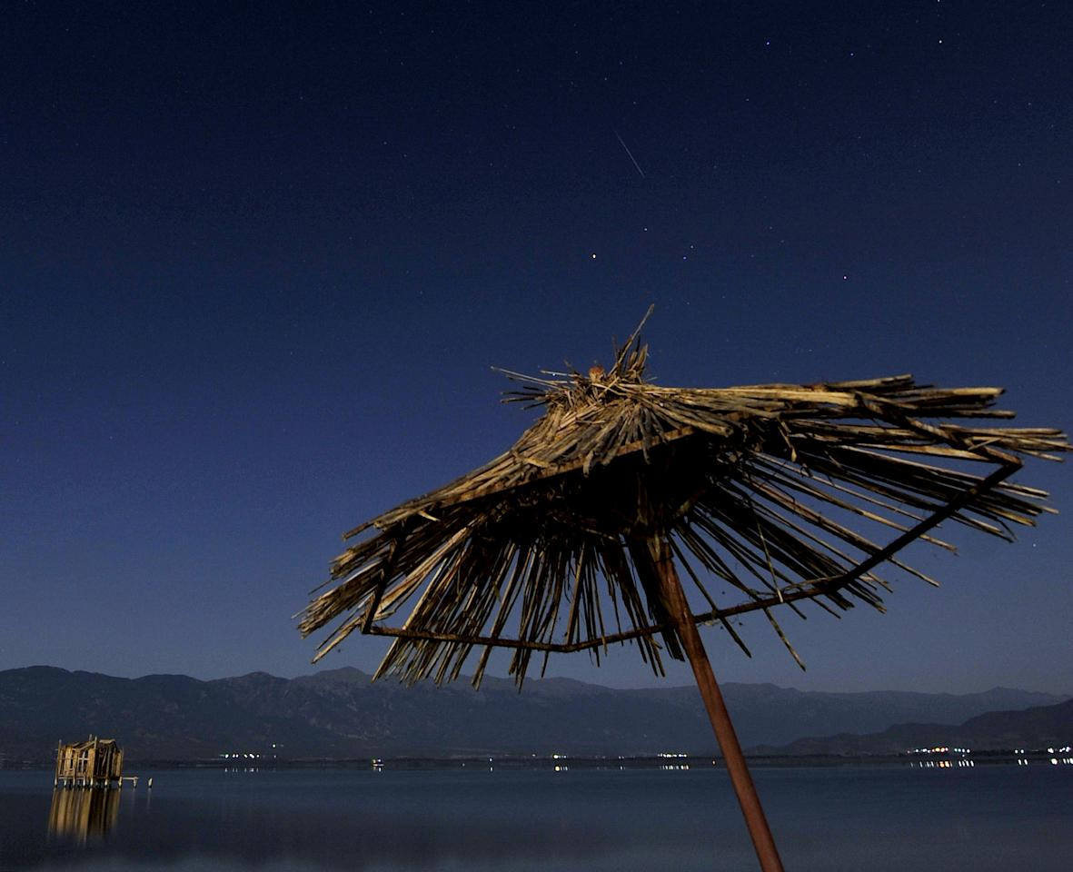 A meteor shines while entering the earth's atmosphere, center top, during the Perseid Meteor Shower observed early Saturday, Aug. 13, 2011, in this long exposure picture taken from Dojran Lake shore in southeastern Macedonia. (AP Photo/Boris Grdanoski)