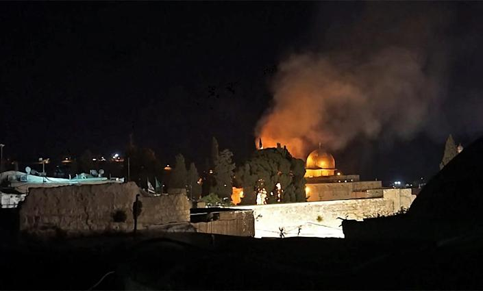 A grab from an AFPTV video shows a tree on fire near the Dome of the Rock mosque in Jerusalem's Al-Aqsa mosque complex on May 10, 2021, following renewed clashes between Palestinians and Israeli police at the scene.
