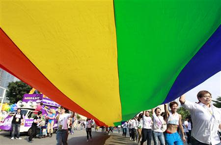 Participants hold a giant rainbow flag during the Taiwan LGBT Pride Parade in Taipei