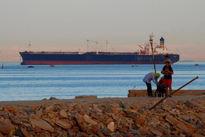 People walk on the beach as a container ship crosses the Gulf of Suez towards the Red Sea before entering the Suez Canal, in El Ain El Sokhna in Suez, east of Cairo, Egypt April 24, 2017. Picture taken April 24, 2017. REUTERS/Amr Abdallah Dalsh