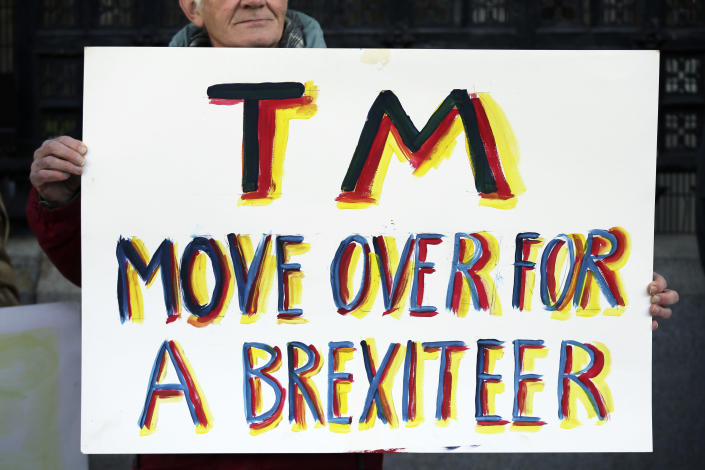 Pro-Brexit demonstrators who oppose Theresa May hold placards outside the Houses of Parliament. (AP Photo/Tim Ireland)