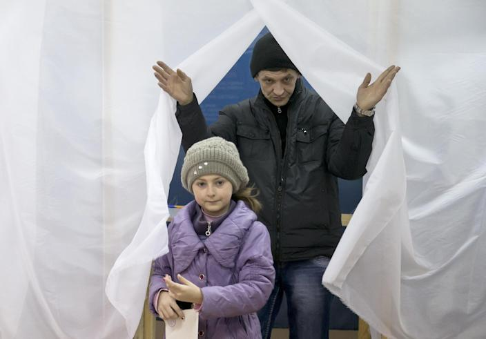 A man and child exit a voting booth after casting a vote in the Crimean referendum in Simferopol, Ukraine, Sunday, March 16, 2014. Residents of Ukraine's Crimea region are voting in a contentious referendum on whether to split off and seek annexation by Russia. (AP Photo/Vadim Ghirda)