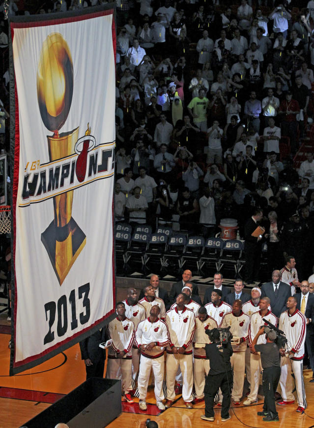 Miami Heat players and coaches watch as the 2013 NBA championship banner is raised before the Heat's season-opener basketball game against the Chicago Bulls on Tuesday, Oct. 29, 2013, in Miami. (AP Photo/Miami Herald, Charles Trainor Jr.)