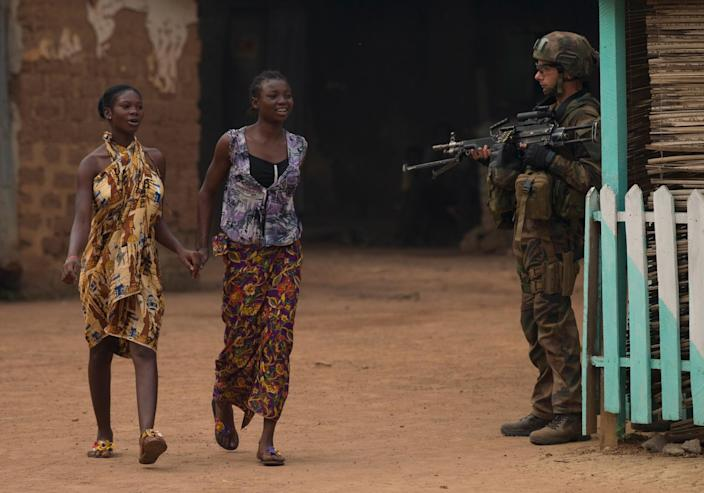 Girls hold hands as they walk past a French soldier holding a position, during an operation to secure part of the Miskine neighborhood, in Bangui, Central African Republic, Thursday, Dec. 26, 2013. The spokesman for an African Union peacekeeping force says six Chadian peacekeepers were killed and 15 were wounded, after being attacked Wednesday.(AP Photo/Rebecca Blackwell)
