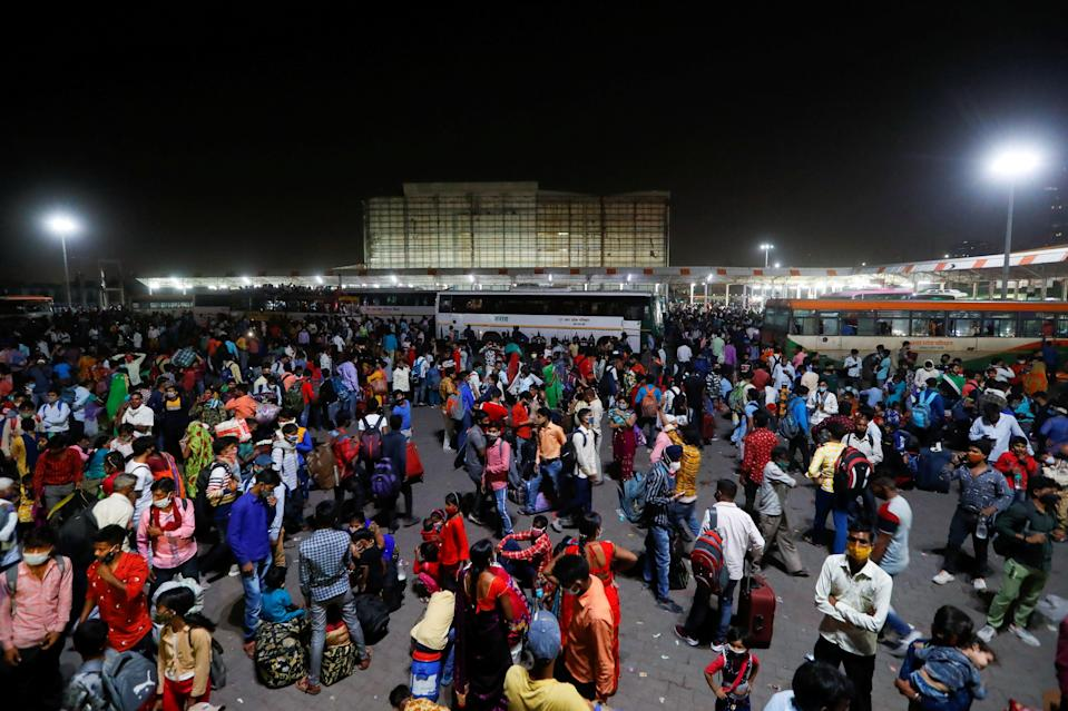 <p>Migrant workers gather at a bus station to board buses to return to their villages after Delhi government ordered a six-day lockdown to limit the spread of the coronavirus disease in Ghaziabad on the outskirts of New Delhi, India on 19 April</p> (Reuters)