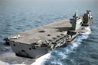 "<p>The U.K. has two aircraft carriers currently under construction. There's the <em>Queen Elizabeth</em>, due to become operational in 2020, and <em>Prince of Wales</em>, due in 2022. They will be the largest ships ever built for the Royal Navy.<br></p><p>Once completed, the carriers will be 920 feet long and displace 65,000 tons apiece. Conventionally powered, they will operate both gas turbine and diesel engines. A high level of automation will keep the number of sailors manning each ship to just 679, with that number increasing to 1,600 with the air wing embedded.</p><p><em>Queen Elizabeth</em> and <em>Prince of Wales</em> will feature a ski jump to assist jet takeoff instead of catapults. Each carrier will carry approximately 12 F-35 Joint Strike Fighters and 4 helicopters on peacetime cruises, with the capability to surge to 36 F-35s in wartime. Alternately, the ships can operate a mix of Apache, <a href=""https://en.wikipedia.org/wiki/AgustaWestland_AW101"" rel=""nofollow noopener"" target=""_blank"" data-ylk=""slk:Merlin"" class=""link rapid-noclick-resp"">Merlin</a>, Chinook, and Wildcat helicopters to land and support a <a href=""https://en.wikipedia.org/wiki/Royal_Marines"" rel=""nofollow noopener"" target=""_blank"" data-ylk=""slk:Royal Marine"" class=""link rapid-noclick-resp"">Royal Marine</a> landing force. </p>"