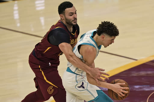 Cleveland Cavaliers' Larry Nance Jr., left, fouls Charlotte Hornets' LaMelo Ball during the first half of an NBA basketball game Wednesday, Dec. 23, 2020, in Cleveland. (AP Photo/Tony Dejak)