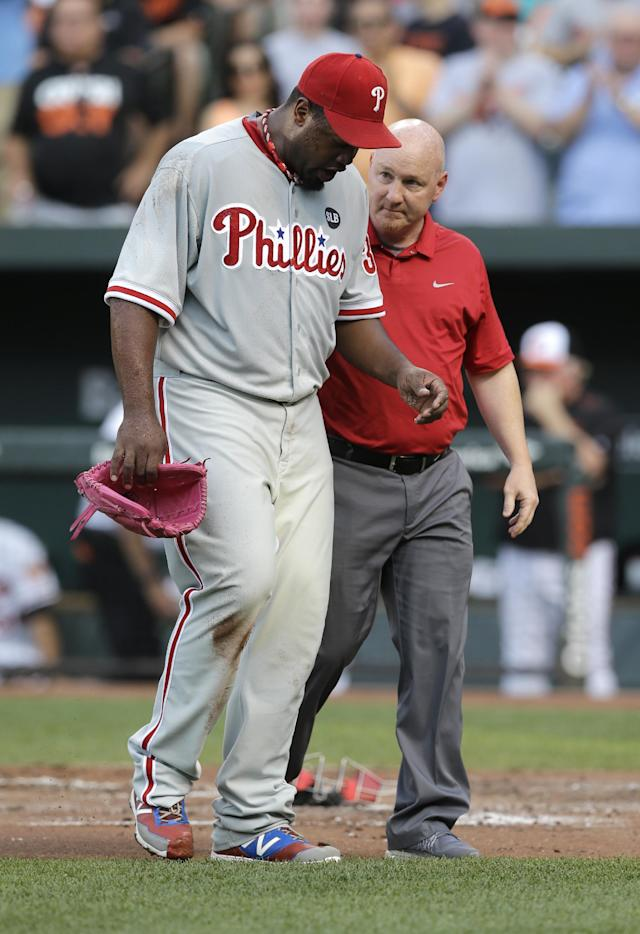 Philadelphia Phillies starting pitcher Jerome Williams, left, is assisted off the field after injuring himself while trying to tag out Baltimore Orioles' Ryan Flaherty at home plate in the first inning of an interleague baseball game, Tuesday, June 16, 2015, in Baltimore. Williams gave up six runs before he left the game with an injury in the first inning. (AP Photo/Patrick Semansky)