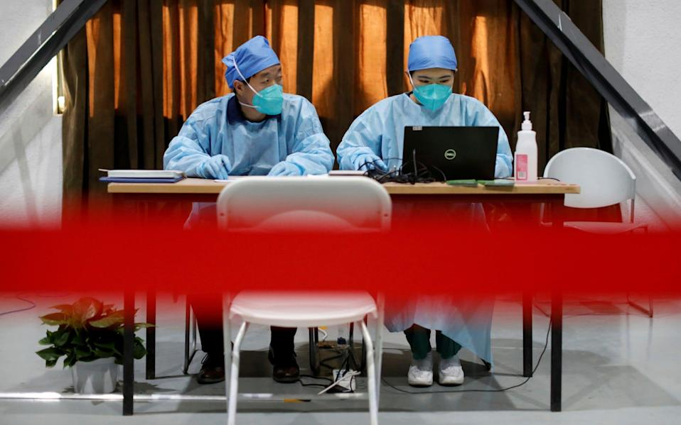 Medical workers wait to register people before they receive a dose of a coronavirus vaccine, in Beijing - Reuters