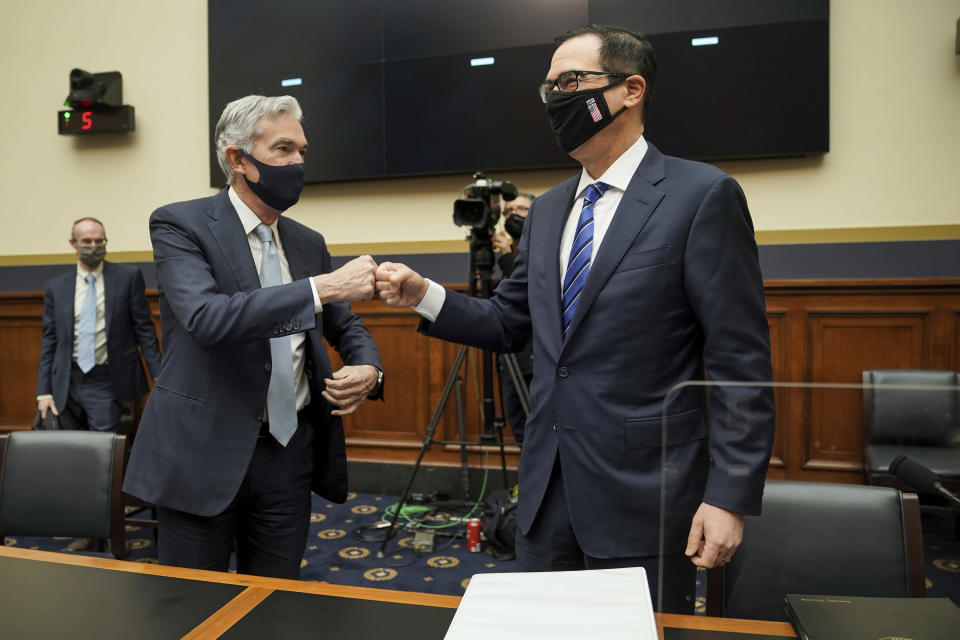 Federal Reserve Chairman Jerome Powell fist bumps Treasury Secretary Steven Mnuchin after a House Financial Services Committee hearing on Capitol Hill in Washington, Wednesday, Dec. 2, 2020. (Greg Nash/Pool via AP)