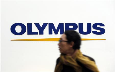 A man passes a logo of Olympus Corp outside the company's showroom in Tokyo