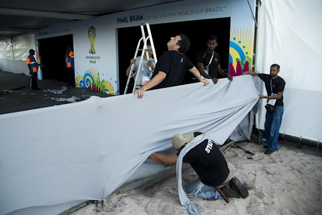 Workers arrange the entrance of the large tent where the 2014 World Cup draw will take place in Costa do Sauipe, Brazil, Wednesday, Dec. 4, 2013. World Cup organizers say they have spent $11 million to organize the 90-minute show that will be beamed around the world on Friday. The mammoth white tent that has been erected on the sand is bigger than most of the world's cathedrals. (AP Photo/Victor R. Caivano)