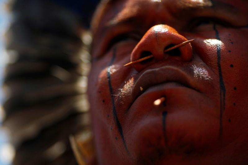 FILE PHOTO: An indigenous man from ethnic group Tupinamba attends a protest to defend indigenous land, outside Brazil's Supreme Federal Court in Brasilia